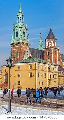 KRAKOW, POLAND - JANUARY 23, 2016: Tourists visit the Wawel Hill where the Royal Castle is located. In the background the Cathedral Basilica of St. Stanislaus and Wenceslas.
