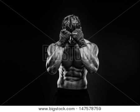 Unrecognizable topless man in fighting gloves covering face with fists on black background. Isolate.