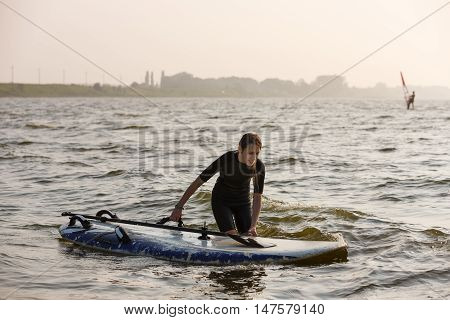 Young windsurfer training in the summer sea