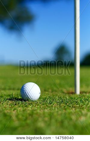 a golf ball near a hole with golf course golf pole