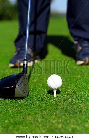 a golfer is about to strike a golf ball on a tee with golf club