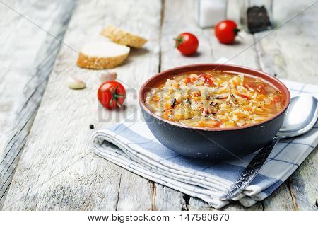 wild rice chickpeas tomatoes cabbage soup on wood background