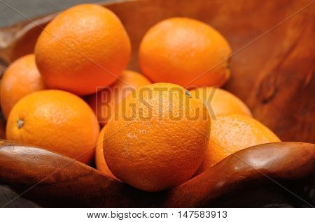 A wooden bowl filled with oranges with shallow dept of field