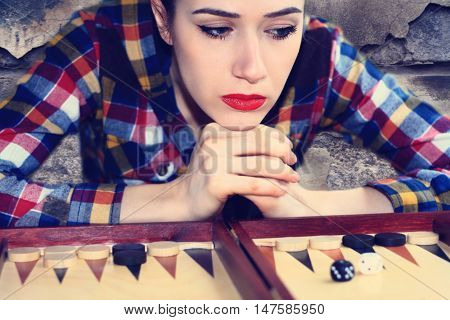Young girl playing backgammon in a historic building.