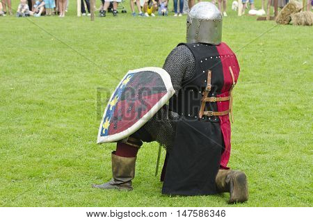 Knight actor with armor and shield in medieval festival in town