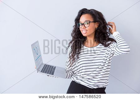 Cheerful user. Glad delighted woman using laptop and expressing gladness while standing isolated on white background