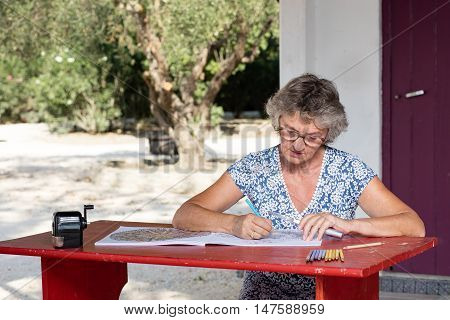 Elder woman drawing at a red desk