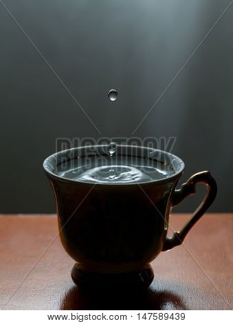 Blue water drops, splashing in the vintage cup. Classic wooden table. Frozen motion. soft focus