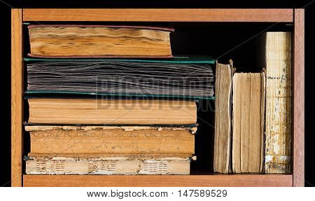 Book shelf on balck background. Vintage books collection, antique textured covers. aged wooden frame. Library scene
