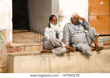 Jodhpur India - 2015 January 1 : Two indian men sitting in the courtyard of a Hinduist temple in the town of Jodhpur Rajasthan India