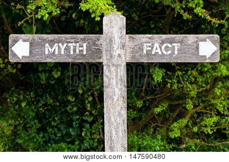 Wooden signpost with two opposite arrows over green leaves background. Myth versus Fact directional signs Choice concept image poster