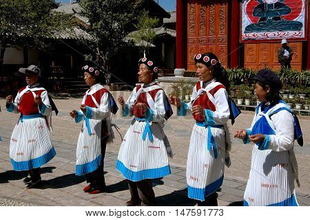 Shu He China - April 26 2006: A group of Naxi women in traditional clothing perform a native dance in the courtyard of a village home