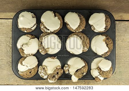 Top down view of one dozen freshly baked home made muffins with brown frosting inside muffin tin on wooden table
