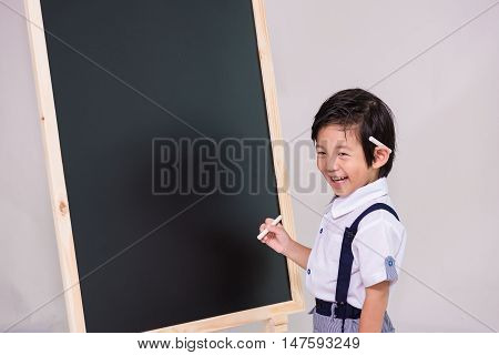 Close up of smart asian boy in white shirt try to writing on the wooden blackboard.