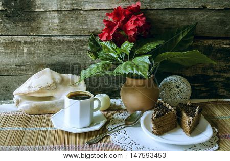 Slices of chocolate, cake black coffee and Chinese rose in the clay pot on straw carpet