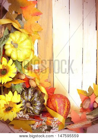 Thanksgiving or fall background with gourds autumn leaves twigs and sunflowers on a rustic wooden background with a vintage filter applied. Vertical orientation with copy space.