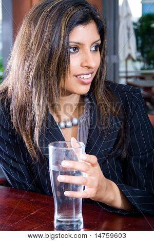 Portrait of beautiful business woman holding glass of water