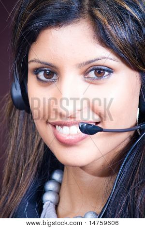 Closeup face of smiling indian business woman with headphones
