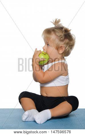 little girl eating green apple on white background