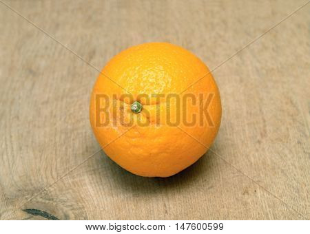 Still-life with ripe orange on brown wooden surface front view horizontal closeup