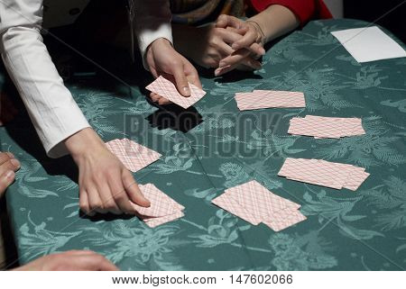 Croupier dealing cards in a poker game placing them face up on the green baize of the gaming table