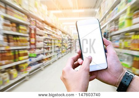 Human using Mobile Phone with blank screen on Department store blurred background