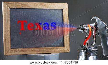 Air spray painting the  Texas blackboard sign.