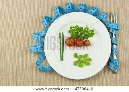 Strict diet against obesity. Dietary vegetable diet. Tomatoes on a plate. Raw vegetables on a white plate and a measuring tape.