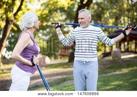 Whole life together. Likable aged couple looking happy together while working-out