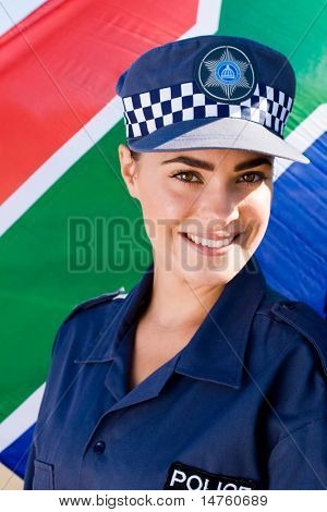 smiling young south african policewoman in front of a south african flag