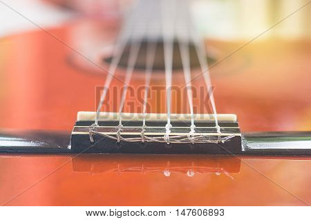close-up of classical guitar bridge and string
