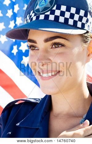 smiling american female police officer portrait, background is US flag
