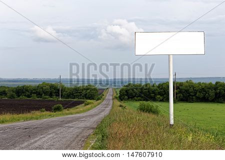 Blank billboard on roadside. Copy space for your text message public information advertising. Mock up empty banner in rural areas. Rural view on blurred background. Shallow focus.