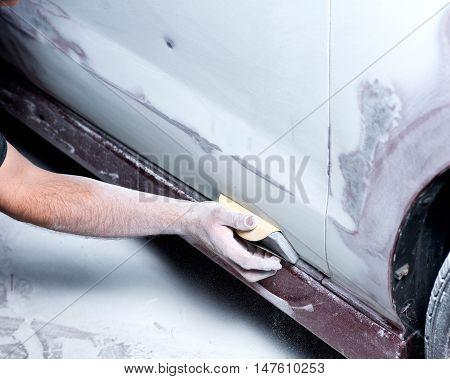 Worker hand sanding filler preparing for repaint