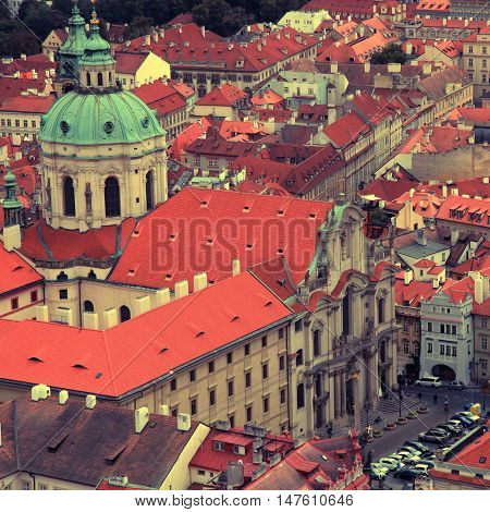 Panorama of Prague Old Town with red roofs and St. Nicholas Church in the quarter of Mala Strana Czech Republic. square vintage toned image