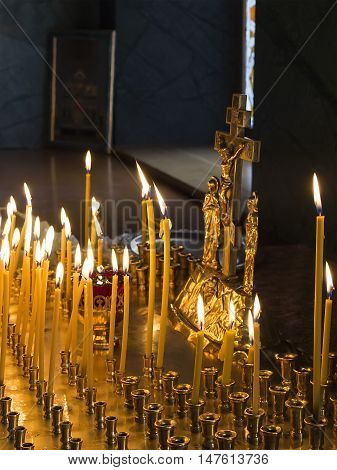 Lighting candles for the dead before the crucifixion of Christ in orthodox temple. Commemoration of dead concept. Selective focus on candles.