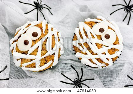 Funny mummy cupcakes on a white background with spiders
