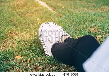 female feet on green grass in the park
