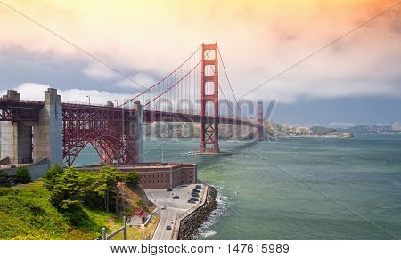 The iconic golden gate bridge over San Francisco Bay with the Marin Headlands in the background and Fort Point in the foreground on a sunny blue sky day.