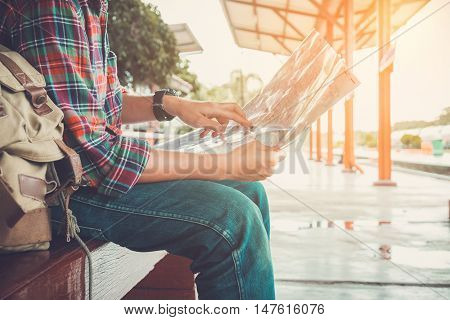 young man traveler sitting with map choose where to travel waiting for train vintage tone