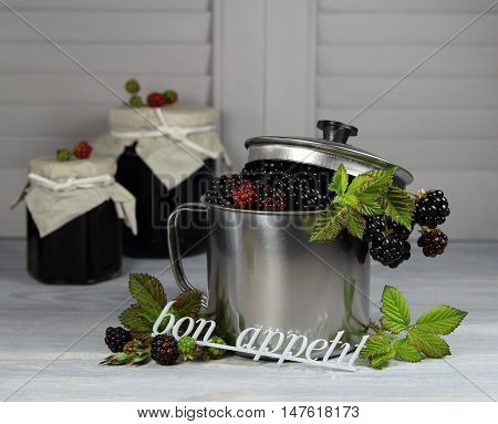 blackberry in a metal mug with banks of jam and an inscription bon appetit