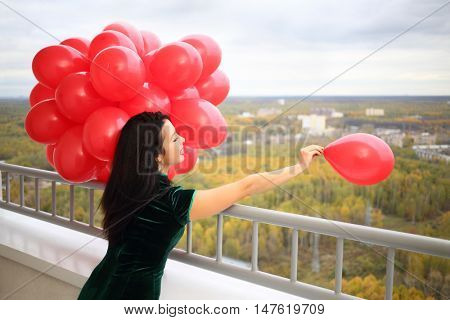 Young woman in green dress holds many red balloons and throws away one on balcony