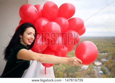 Woman in green dress holds many red balloons and throws away one on balcony
