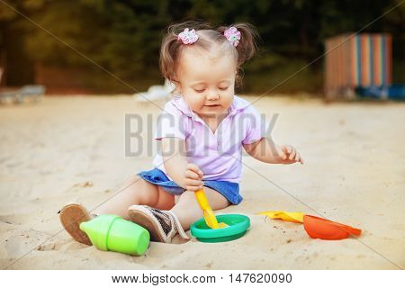 beautiful baby playing in the sandbox toys. The concept of childhood and development.