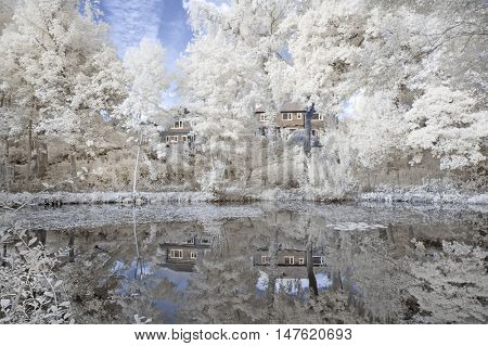 Infrared landscape showing a lake with white foliage around it with a reflection in Cheshire England [infra red image]
