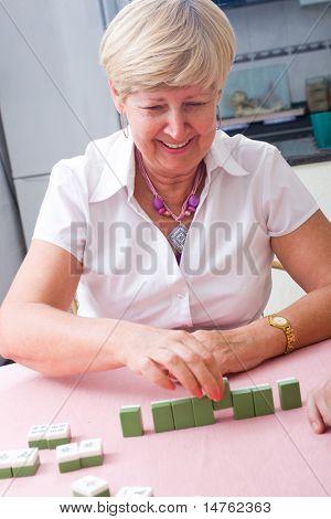elegant elderly lady playing mah-jong game