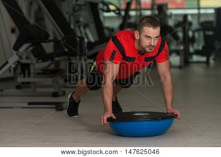 Young Man Doing Exercise On Bosu Balance Ball
