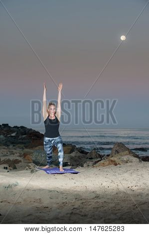 Portrait view of female athlete practicing Crecent Moon Pose under full Harvest Moon.