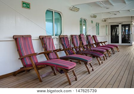 Colorful wooden deck chairs are set out for passengers on the promenade deck of a cruise ship.