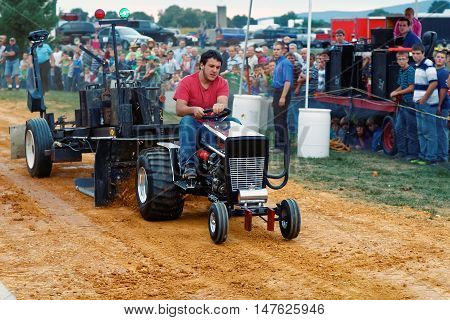 MYERSTOWN PENNSYLVANIA - SEPTEMBER 16 2016: A young man drives a modified lawn tractor at Myerstown East End Days. The tractor pull is an annual community event.